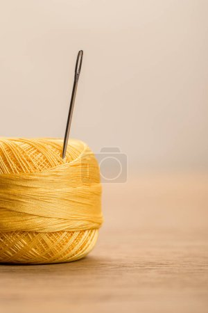 Photo for Selective focus of yellow cotton knitting yarn ball with needle isolated on beige with copy space - Royalty Free Image