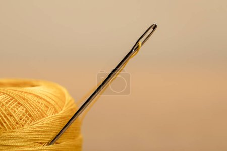 Photo for Selective focus of yellow cotton knitting yarn ball on beige with copy space - Royalty Free Image