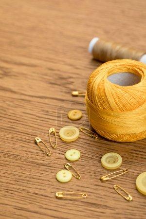 Photo pour Coton tricot boule de fil avec des boutons de vêtements et des épingles de sécurité sur table en bois - image libre de droit