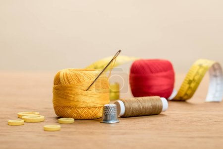 Photo for Cotton knitting yarn balls with needle and thimble on wooden table isolated on beige - Royalty Free Image