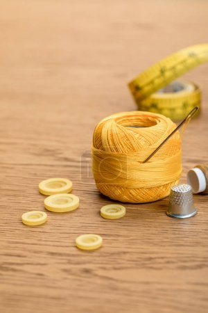 Photo for Cotton knitting yarn ball with clothing buttons and thimble on wooden table - Royalty Free Image