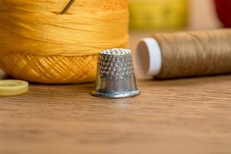 Foto de Vista de cerca del dedal con bola de hilo y bobina de hilo en la mesa de madera - Imagen libre de derechos