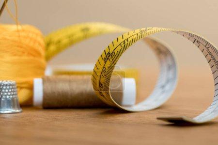 Photo pour Mise au point sélective de la bande de mesure avec bobine de fil sur la table en bois - image libre de droit
