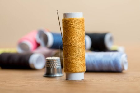 Photo for Selective focus of cotton thread coil with needle isolated on beige - Royalty Free Image