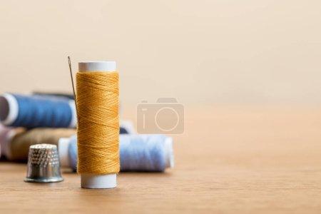 Photo pour Focalisation sélective de bobine de fil de coton avec l'aiguille d'isolement sur le beige avec l'espace de copie - image libre de droit