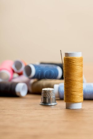 Photo for Selective focus of cotton thread coil with needle isolated on beige with copy space - Royalty Free Image