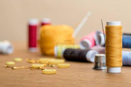 Photo pour Foyer sélectif de bobine de fil avec boutons de vêtements sur table en bois isolé sur beige - image libre de droit