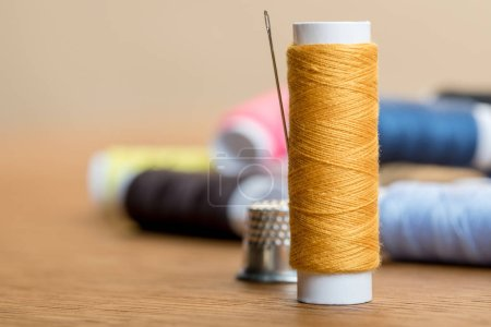 Photo for Selective focus of thread coil with needle on table isolated on beige with copy space - Royalty Free Image