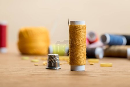Photo for Selective focus of thread coil with thimble on wooden table isolated on beige - Royalty Free Image