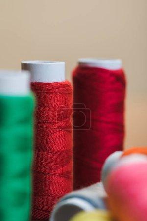Photo pour Concentré sélectif de bobines de fil de coton rouge isolées sur beige - image libre de droit