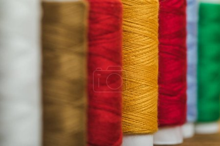 selective focus of colorful cotton thread coils in row with copy space