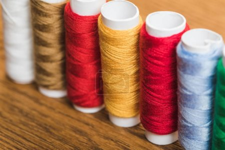 Photo for Colorful cotton thread coils in row on wooden surface - Royalty Free Image