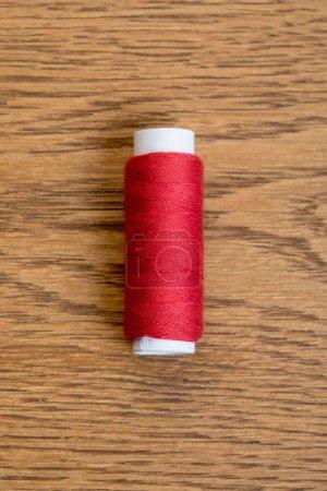 Photo pour Vue de dessus de bobine de fil de coton rouge sur la surface en bois - image libre de droit
