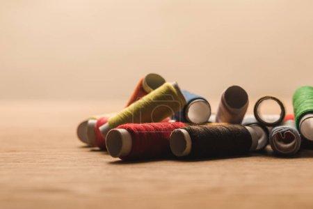 Photo pour Mise au point sélective de bobines de fil de coton colorés sur la table d'isolement sur beige - image libre de droit