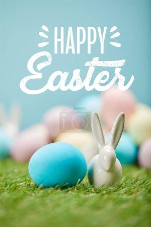 Photo pour Oeuf peint en bleu près de lapin décoratif sur herbe verte avec lettrage de Pâques heureux ci-dessus - image libre de droit