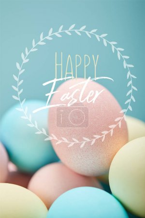 Photo for Pile of multicolored painted chicken eggs with happy Easter lettering in circle on blue background - Royalty Free Image