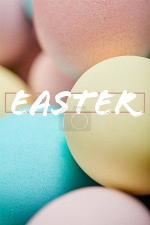 Photo for Close up of pile of multicolored painted chicken eggs with Easter lettering - Royalty Free Image