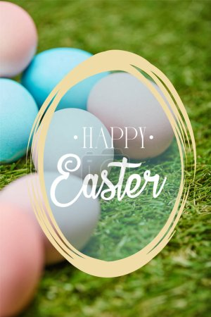 Photo for Pile of multicolored painted chicken eggs with happy Easter lettering on green grass - Royalty Free Image