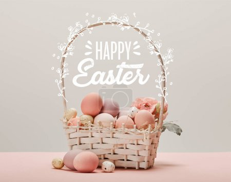 Photo for Wicker basket with pink painted eggs, flowers and happy Easter lettering on grey background - Royalty Free Image