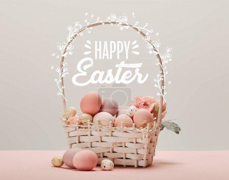 Photo pour Panier en osier avec oeufs peints en rose, fleurs et joyeux lettrage de Pâques sur fond gris - image libre de droit