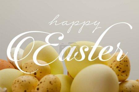 Photo pour Oeufs de poulet et de caille peints jaunes avec le lettrage joyeux de Pâques sur le fond gris - image libre de droit