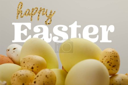 Photo for Yellow painted eggs with happy Easter lettering on grey background - Royalty Free Image