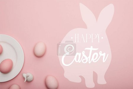 Photo for Top view of painted eggs and white decorative bunny near plate on pink background with happy Easter lettering - Royalty Free Image