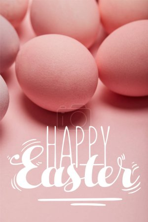 Photo pour Painted pink eggs on pink surface with happy Easter lettering - image libre de droit