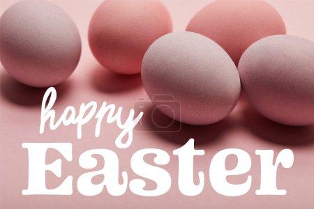 Photo pour Peint des oeufs roses sur la surface rose avec le lettrage de Pâques heureux blanc - image libre de droit