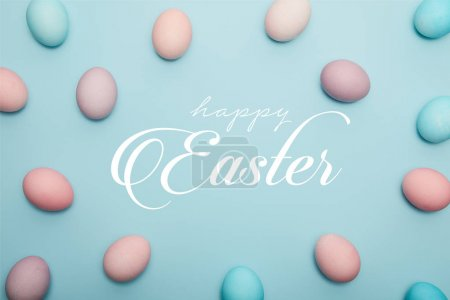 Photo for Top view of painted eggs on blue background with happy Easter lettering - Royalty Free Image