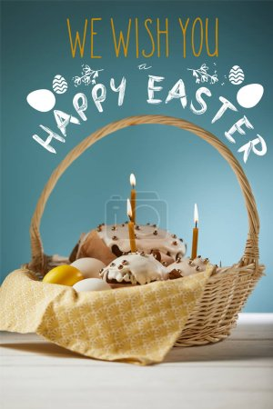 Photo pour Traditional Easter cakes with burning candles and chicken eggs in wicker basket on blue background with we wish you happy easter lettering - image libre de droit