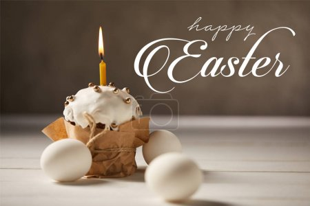 Photo for Traditional Easter cake with burning candle and white chicken eggs on brown background with happy easter lettering - Royalty Free Image