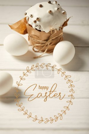 Photo for Traditional Easter cake and white chicken eggs on white wooden table with happy easter lettering - Royalty Free Image