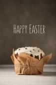 """Постер, картина, фотообои """"традиционный украшенный Пасхальный торт в ремесленных бумаги на белом столе с счастливой Пасхи надписи на коричневом фоне"""""""