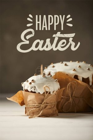 Photo for Traditional decorated Easter cakes in craft paper on white table with happy easter lettering on brown background - Royalty Free Image