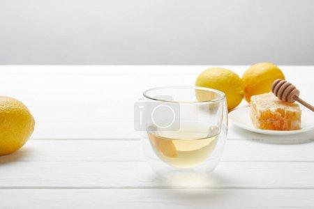 Photo pour Verre transparent avec le thé vert, les citrons et le nid d'abeilles sur la table en bois blanche - image libre de droit
