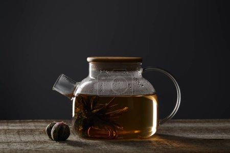 Foto de Tetera transparente con té en flor y bolas de té en la mesa de madera aislada en negro - Imagen libre de derechos
