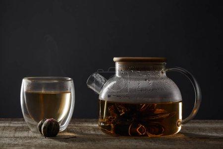Foto de Tetera transparente y vidrio con té en flor sobre mesa de madera aislado en negro - Imagen libre de derechos