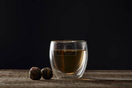 Foto de Vidrio transparente con té en flor aislado en negro con espacio de copia - Imagen libre de derechos