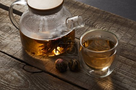Photo for Transparent teapot and glass with chinese blooming tea on wooden table - Royalty Free Image