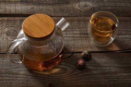 Foto de Tetera transparente y vidrio con té chino en flor sobre mesa de madera - Imagen libre de derechos