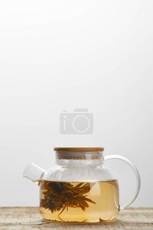 Foto de Tetera de vidrio con té de floración china en la mesa de madera aislada en gris con espacio de copia - Imagen libre de derechos