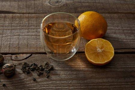 Foto de Vaso de té tradicional de floración china, limones y bolas de té en la mesa de madera - Imagen libre de derechos