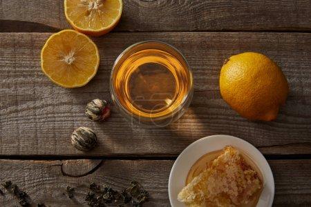 Foto de Vista superior del té chino en flor en vidrio, limones y panal en la mesa de madera - Imagen libre de derechos