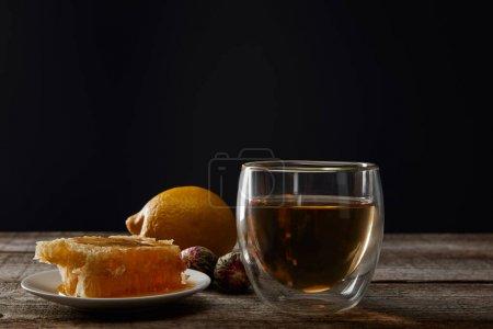 Foto de Cristal transparente con té en flor, panal y limón sobre mesa de madera aislado en negro - Imagen libre de derechos