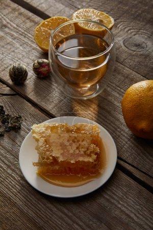 Foto de Vaso de té tradicional de floración china, limones y panal en superficie de madera - Imagen libre de derechos