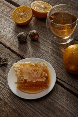 Foto de Vaso de té tradicional de floración china, limones y panal en la mesa de madera - Imagen libre de derechos