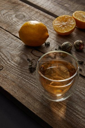 Photo for Glass of traditional chinese blooming tea and lemons on wooden table - Royalty Free Image