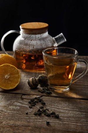 Foto de Tetera transparente con té en flor, taza, limones y bolas de té en una mesa de madera aislada en negro - Imagen libre de derechos