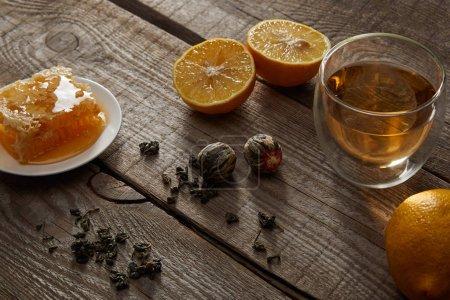 Foto de Vaso de té chino en flor, limones y panal sobre mesa de madera - Imagen libre de derechos